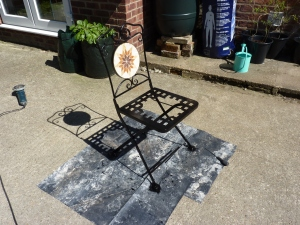 Look how careful my husband is now - he even put down a sheet of DPC under the garden chair in order to paint it. Shortly our shabby chair was resplendently painted in Hammerite black.
