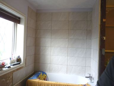 Chris cut all the tricky tiles and I finished the bath surround area - tomorrow will be grouting day!